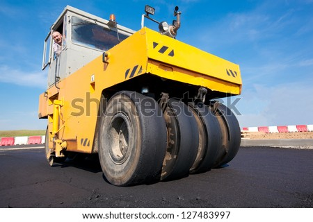 Compactor - Pneumatic Tyred Roller during asphalt paving. New road construction - stock photo