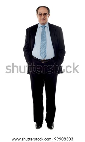 Company manager wearing black suit standing in front of camera with hands in pocket - stock photo