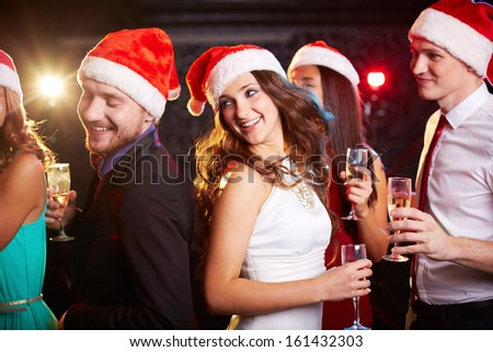 Company of friends in Santa caps holding flutes of champagne while dancing at Christmas party - stock photo