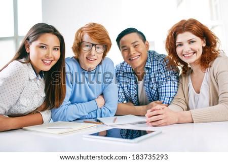 Company of smart groupmates looking at camera - stock photo