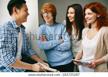Company of smart groupmates talking in college - stock photo
