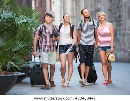 Company of travelers with travel bags walking the city - stock photo