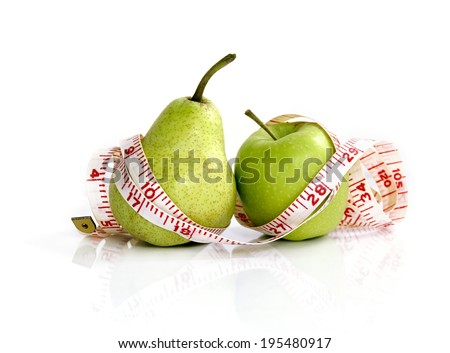 compare an apple to a pear - measuring tape on apple and pear (manual focus) - stock photo