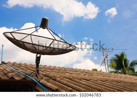 Compare Old analog antennas  VS modern analog  satellite with blue sky - stock photo