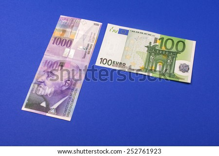 comparison of Swiss francs and euros with place for text lying on blue background - stock photo