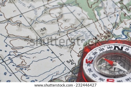 Compass and map. The magnetic compass is located on a topographic map. - stock photo