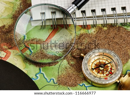 compass and  notebook on the map with sand - stock photo