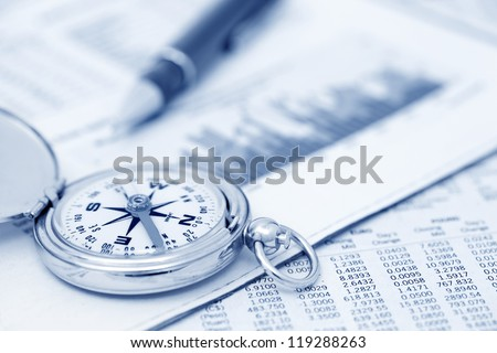 Compass and papers about financial issues - stock photo