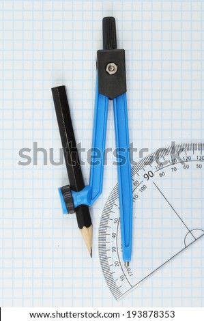 Compass and protractor on graph paper - stock photo
