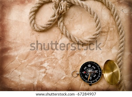 compass and rope on a background an old paper - stock photo