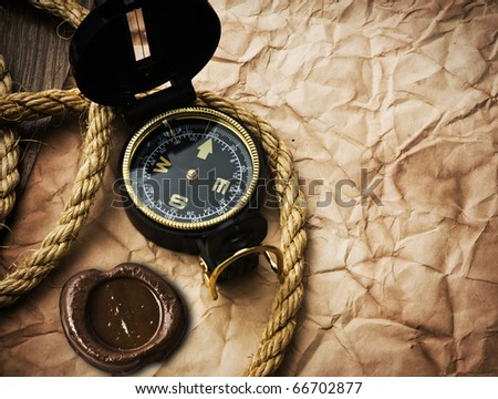 compass and rope on old paper background - stock photo