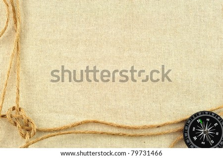 compass and rope on with a canvas of burlap - stock photo