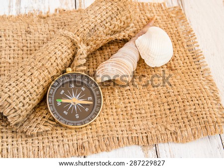 Compass and seashell on burlap sack on wooden background - stock photo