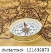 compass gold color on the old map with coins - stock photo