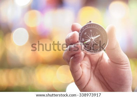 compass in hand on defocused abstract bokeh lights christmas background, blur of bokeh circle light christmas festive backdrop concept. - stock photo