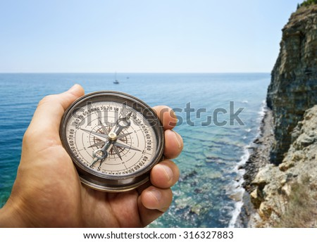 Compass in the hand on the nature background. - stock photo