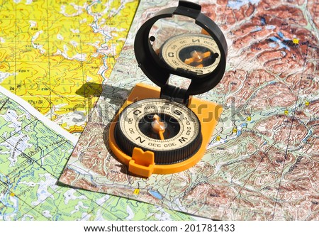 Compass lies on a topographic map. Compass on the map - this is the open door to the country adventure. - stock photo