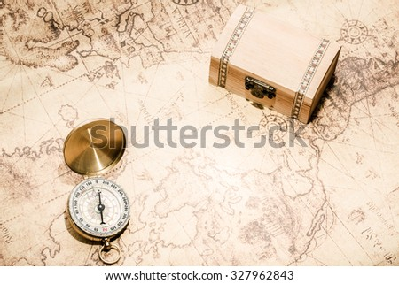 compass lying on vintage map with treasure chest. - stock photo