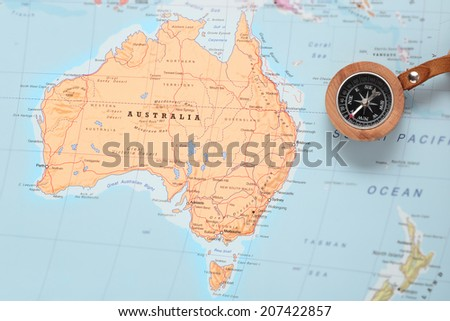 Compass on a map pointing at Australia and planning a travel destination - stock photo