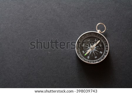 Compass on black paper background - stock photo