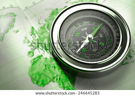 Compass on map background in green toning - stock photo