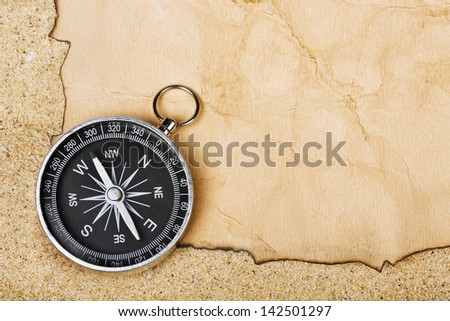 Compass on old paper against the background of sand - stock photo