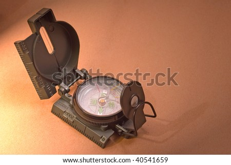 Compass on parchment paper with low light - stock photo