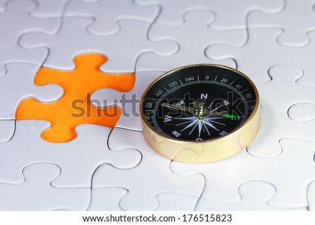 Compass on puzzle with one piece missing - stock photo