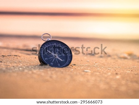 compass on the beach with sunrise - stock photo