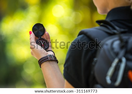 Compass on tourism woman hand against tropical landscape. - stock photo