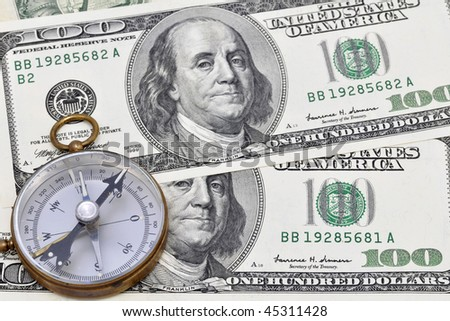 Compass on two hundred dollars background. - stock photo