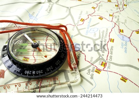 Compass over a trekking map. Color image - stock photo