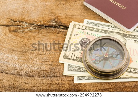 Compass, passport and money on wood background. - stock photo