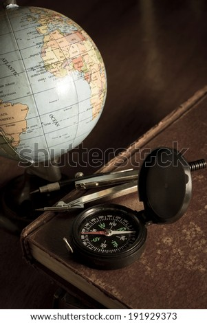 Compass with globe on antique book,vintage style color. - stock photo