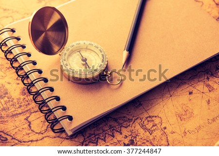Compass with note book and pencil on old map vintage process style - stock photo