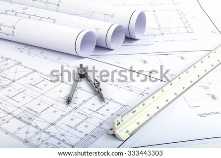 Compasses and Architect scale ruler placed on the desk, filled with building plans. In order to work in a building - stock photo