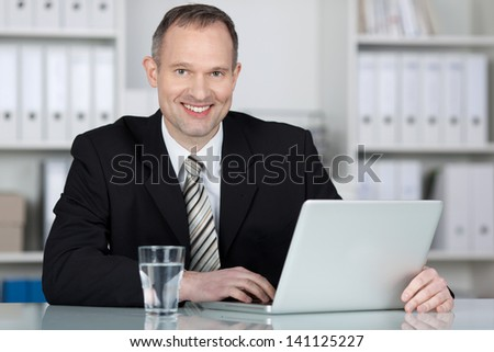 Competent businessman working with laptop on the table - stock photo