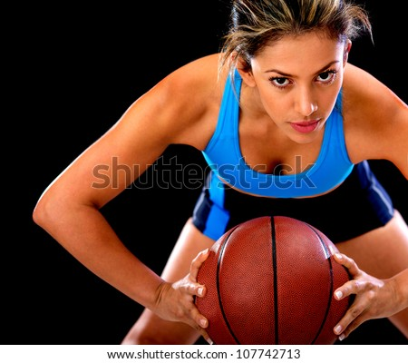 Competitive basketball player holding the ball - isolated over black background - stock photo