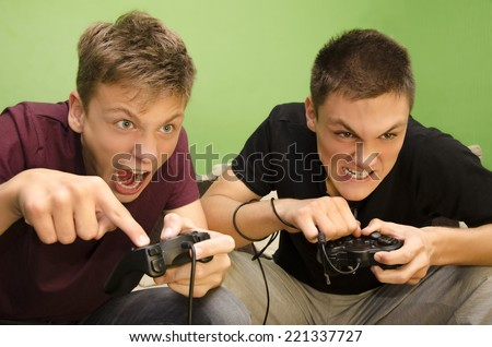 Competitive brothers playing video games funny - stock photo