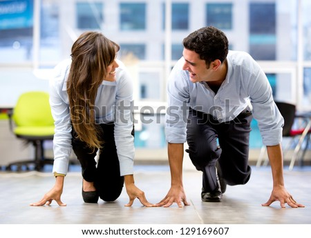 Competitive business couple ready for a race at the office - stock photo