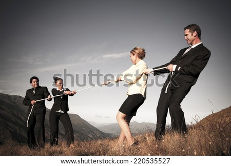 Competitive business people struggling to win tug-of-wars. - stock photo