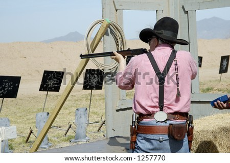 Competitor shooting a lever action rifle in a cowboy shoot competition. - stock photo