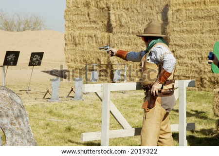 Competitor shooting a single-action pistol in a cowboy shoot competition. - stock photo
