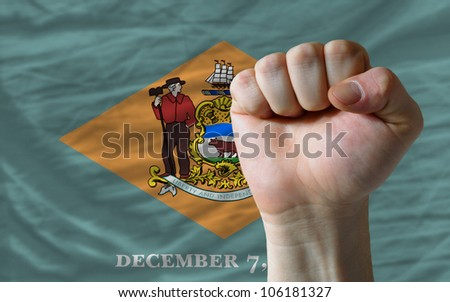 complete american state of delaware flag covers whole frame, waved, crunched and very natural looking. In front plan is clenched fist symbolizing determination - stock photo