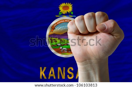 complete american state of kansas flag covers whole frame, waved, crunched and very natural looking. In front plan is clenched fist symbolizing determination - stock photo