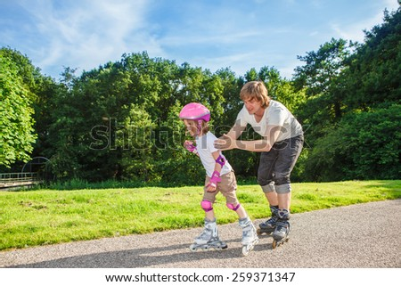Complete beginner roller skating, her father helping her - stock photo