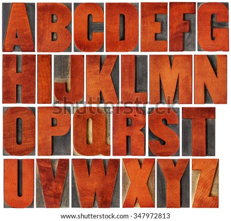 complete English alphabet set - a collage of 26 isolated vintage wood letterpress printing blocks, scratched and stained by red ink , gothic bold extended font - stock photo