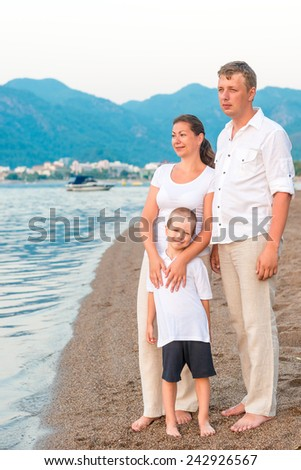 complete family with son on the sea shore - stock photo