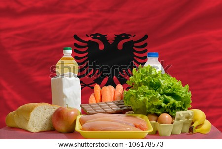 complete national flag of albania covers whole frame, waved, crunched and very natural looking. In front plan are fundamental food ingredients for consumers, symbolizing consumerism - stock photo