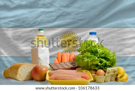 complete national flag of argentina covers whole frame, waved, crunched and very natural looking. In front plan are fundamental food ingredients for consumers, symbolizing consumerism - stock photo